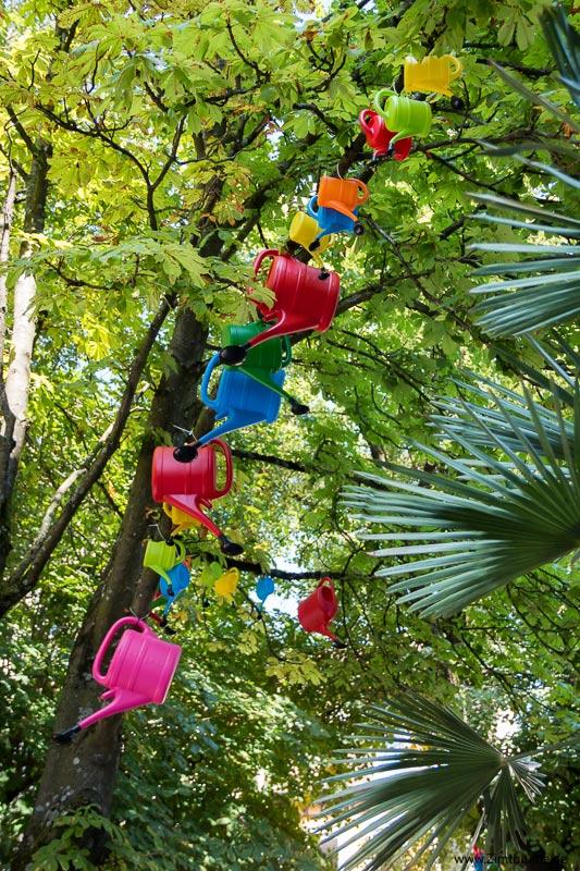 Bunte Giesskannen in den Bäumen
